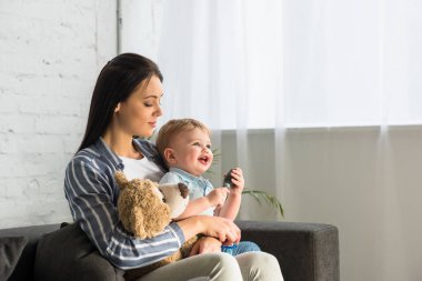 young mother and smiling little baby with teddy bear sitting on sofa at home