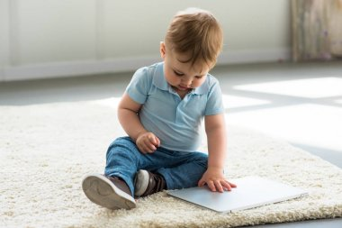 Little baby boy with laptop sitting on floor at home stock vector