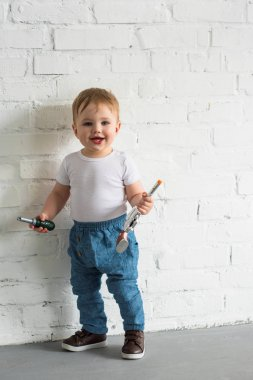 happy little baby boy with toys standing at white brick wall