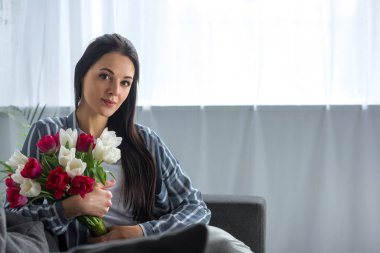 portrait of young woman with bouquet of tulips sitting on sofa at home