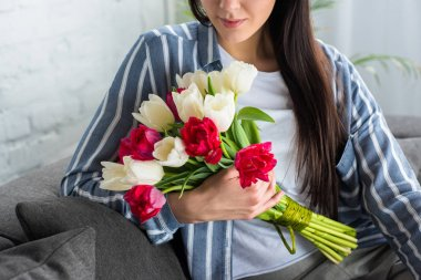 cropped shot of beautiful woman holding bouquet of tulips in hand while sitting on sofa