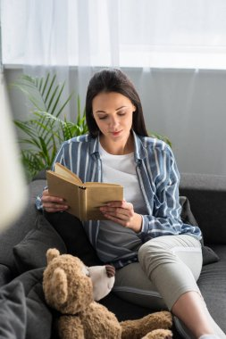 young woman reading book on sofa with teddy bear at home