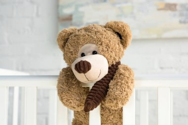 close up view of teddy bear hanging on white wooden baby crib in room