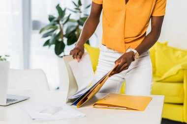partial view of african american woman with folders remote working at home office