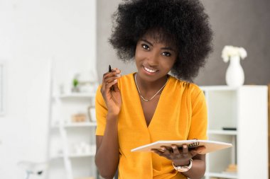 portrait of smiling african american freelancer with notebook at home office
