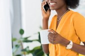 részleges kilátás mosolyogva afro-amerikai csésze kávé beszél a smartphone otthon