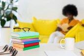 Fotografia fuoco selettivo del mucchio di libri, occhiali, tazza di caffè presso libero professionista sul posto di lavoro e afro-americano sul sofà su sfondo a casa