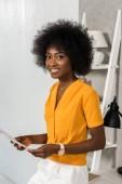 s úsměvem africké americké freelancer s papíry v rukou pohledu kamery domácí kancelář