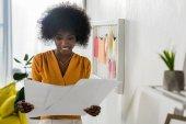 Fotografie Porträt von lächelnden afroamerikanische Freiberufler mit Papiere zu Hause Büro
