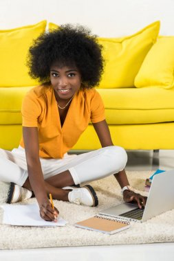 smiling african american freelancer looking at camera while remote working on floor at home