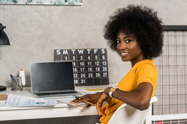 back view of smiling african american female freelancer sitting at table at home office