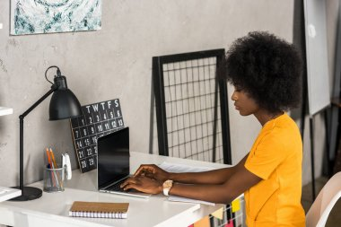 side view of african american female freelancer working on laptop with blank screen at home