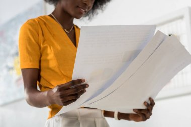 cropped shot of african american freelancer with papers in hands at home office