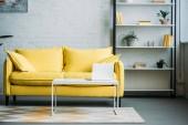 Laptop auf Tisch neben gelbem Sofa im Wohnzimmer
