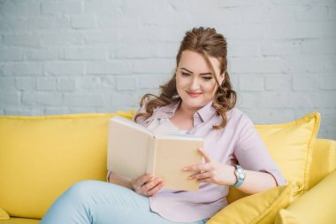 beautiful woman reading book on sofa at home
