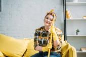 Fotografie krásná žena sedí na pohovce s mopem doma