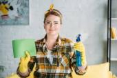 krásná žena držící hadr a stříkací láhev pro čištění v domácnosti