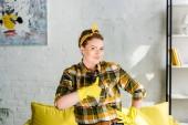 Fotografie krásná žena v gumové rukavice ukazuje palcem při čištění doma