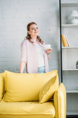 beautiful woman holding cup of coffee and looking away at home