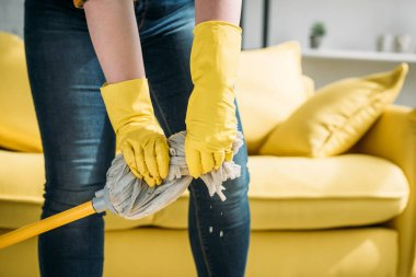 beautiful woman wringing out rag on mop at home