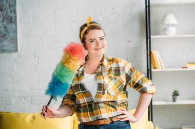 beautiful woman posing with dust brush for cleaning at home