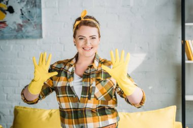 beautiful woman showing hands in rubber gloves for cleaning at home