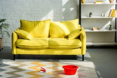 red bucket and cleaning brush on carpet on floor, yellow sofa in living room