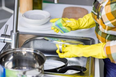 cropped image of woman washing dishes in kitchen