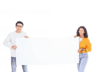 portrait of multicultural teenagers holding blank banner in hands isolated on white