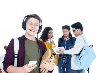 handsome teen student in headphones and with smartphone isolated on white with his friends chatting on background