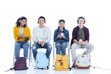 group of teen students in headphones sitting on chairs isolated on white