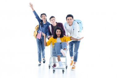 teen students riding their friend on shopping cart isolated on white