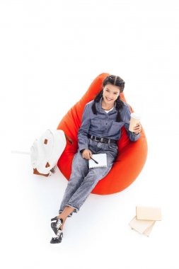 high angle view of teenage student girl studying while sitting on bean bag isolated on white