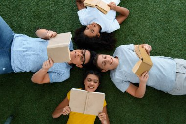 top view of group of teen students reading books on green grass