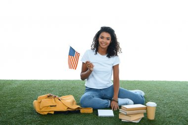 teenage african american student girl with usa flag sitting on grass isolated on white