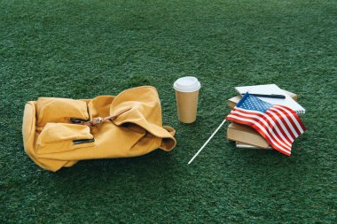 vintage backpack and school supplies with usa flag on green grass