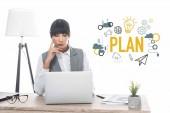 podnikatelka, sedí u stolu a při pohledu na notebook izolovaných na bílém, plán nápis a obchodní ikony