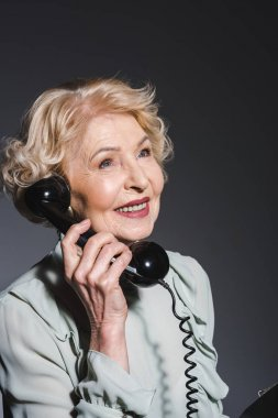 close-up portrait of smiling senior woman talking by vintage phone on dark grey
