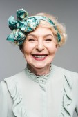 beautiful senior woman in stylish vintage shirt and headband isolated on grey