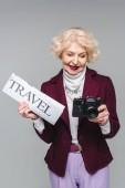 Fényképek gyönyörű magas rangú nő a utazási újság és a film fényképezőgép elszigetelt szürke