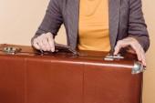 Fotografie zugeschnittene Aufnahme stilvolle Frau schließen Vintage Koffer auf Beige hintergrund isoliert