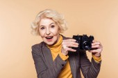 surprised senior woman with film camera isolated on beige background