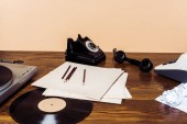 Fotografie rotary phone, vinyl disc, record player and typewriter on wooden table