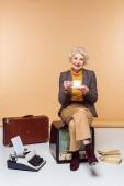 Photo stylish senior woman drinking coffee and sitting on vintage tv near typewriter and suitcase