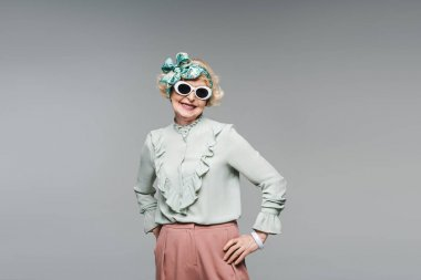 attractive senior woman in stylish headband and sunglasses isolated on grey