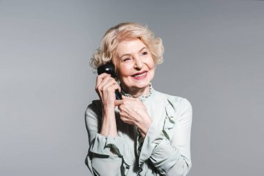 close-up portrait of smiling senior woman talking by vintage phone isolated on grey