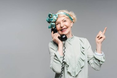 Happy senior woman talking by vintage phone and pointing up isolated on grey stock vector