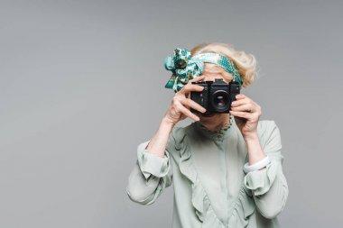 Stylish senior woman taking photo with vintage film camera isolated on grey stock vector