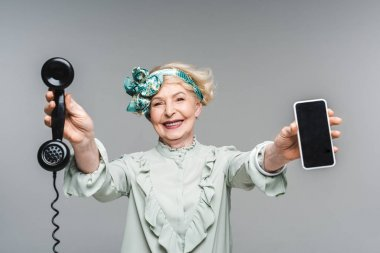 smiling senior woman with vintage phone and smartphone in hands isolated on grey