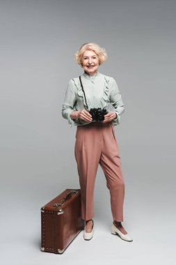 beautiful senior woman with vintage suitcase and film camera on grey